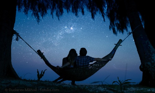 Couple ralaxing in a hammock and enjoying starry sky